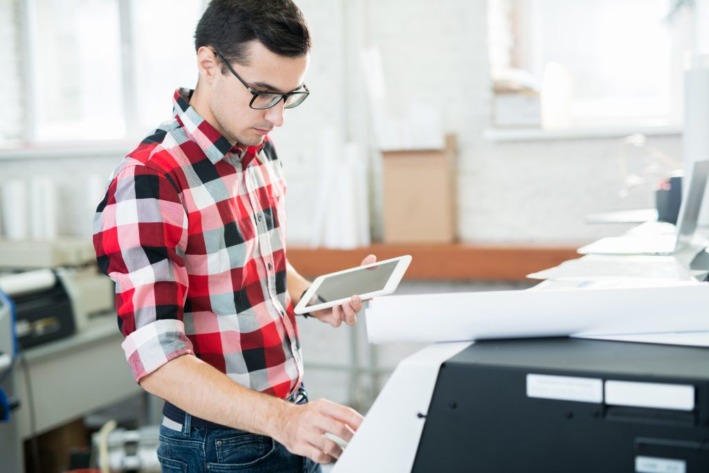 Serious busy handsome male technician in glasses wearing checkered shirt using tablet to operate large format printer in workshop